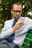 Businessman sitting on bench and chatting Stock Photos
