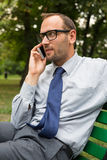 Businessman sitting on bench and chatting. On a cell phone Royalty Free Stock Images