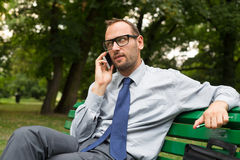 Businessman sitting on bench and chatting on a cell phone. Stock Photography
