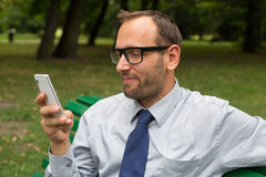 Businessman sitting on bench and chatting on a cell phone. With a happy expression Stock Photo