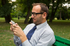 Businessman sitting on bench and chatting on a cell phone  Stock Image