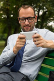 Businessman sitting on bench and chatting on a cell phone. With a happy expression Royalty Free Stock Images