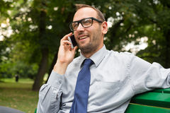 Businessman sitting on bench and chatting on a cell phone. With a happy expression Stock Photos
