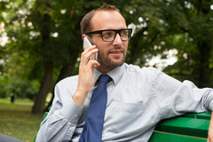 Businessman sitting on bench and chatting on a cell phone. With a happy expression Stock Image