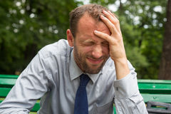 Businessman sitting on a bench with headache in the park. Royalty Free Stock Photography