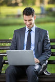 Businessman sitting on bench with laptop. In park Stock Photography
