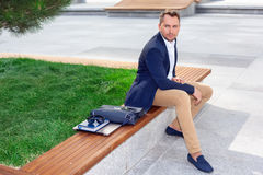Businessman sitting on bench. Looking right Stock Photos