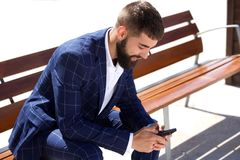 Businessman sitting on bench with mobile phone Royalty Free Stock Photo