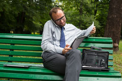 Businessman sitting on bench with mobile phone and tablet. Royalty Free Stock Photo