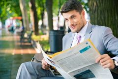Businessman sitting on the bench with newspaper. Smiling businessman sitting on the bench with newspaper and looking at away in park Royalty Free Stock Image