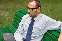 Businessman sitting on a bench. In the park Stock Images