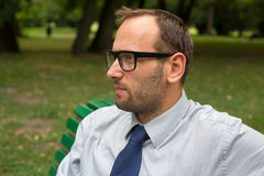Businessman sitting on a bench. In the park Royalty Free Stock Image