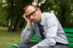 Businessman sitting on a bench in the park. Stock Images