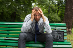 Businessman sitting on a bench in the park. Royalty Free Stock Photo