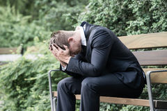 Businessman Sitting On Bench. Photo Upset Young Businessman Sitting On Bench Royalty Free Stock Photos