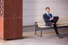 Businessman sitting on bench. Picture of businessman sitting on bench waiting for train Royalty Free Stock Photo