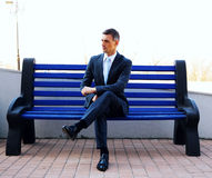 Businessman sitting on bench Stock Images