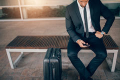 Businessman sitting on bench with suitcase and using smart phone. Young businessman sitting on bench with suitcase and using smart phone. Business executive Royalty Free Stock Image