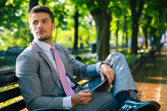 Businessman sitting on the bench with tablet computer. Pensive businessman sitting on the bench with tablet computer outdoors and looking away Royalty Free Stock Photography
