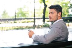 Businessman sitting on the bench with tablet computer. Thoughtful businessman sitting on the bench with tablet computer outdoors and looking away Stock Images