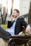 Businessman sitting on a  bench  and talking on the phone on a s. Businessman sitting on a  bench  and talking on the phone in nice sunshine Royalty Free Stock Photos