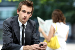 Businessman sitting on bench using his phone Royalty Free Stock Images