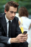 Businessman sitting on bench using his phone Stock Photo