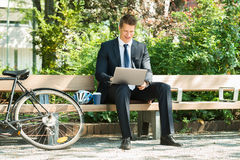 Businessman Sitting On Bench Using Laptop. Happy Male Businessman Sitting On Bench Using Laptop At Park Stock Images