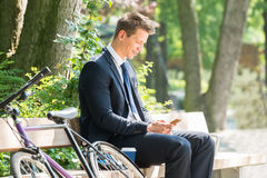 Businessman Sitting On Bench Using Mobile Phone. Young Male Businessman Sitting On Bench Using Mobile Phone At Park Royalty Free Stock Images