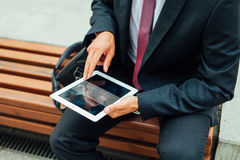 Businessman sitting on a bench and using tablet pc. Close up. Businessman sitting on a bench and using tablet pc. Close up Stock Photo