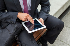 Businessman sitting on a bench and using tablet pc. Close up. Businessman sitting on a bench and using tablet pc. Close up Royalty Free Stock Image