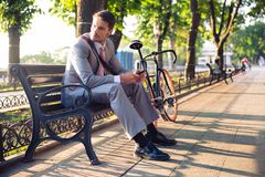 Businessman sitting on the bench. Young businessman sitting on the bench in city park and looking away Stock Image