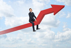 Businessman sitting on big red line graph with an upturned arrow. Businessman sitting on a big red line graph with an upturned arrow on a sky background. Rapid stock image
