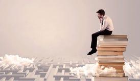 Businessman sitting on books in labirynth Stock Photos