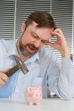 Businessman sitting breaks piggy bank Royalty Free Stock Photos