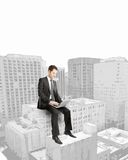 Businessman sitting on building Stock Photos
