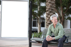 Businessman sitting on a bus bench Stock Images