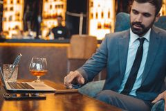 Businessman sitting in a business center bar drinking whiskey getting cigar stock photos