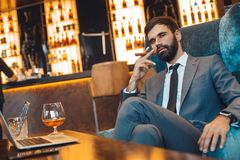 Businessman sitting in a business center bar smoking cigar. Middle-aged man businessman sitting in a business center bar smoking cigar looking camera Royalty Free Stock Image