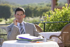 Businessman sitting at caf? table with paperwork Royalty Free Stock Images