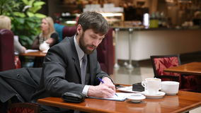Businessman sitting in a cafe drinking coffee. stock video