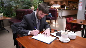 Businessman sitting in a cafe drinking coffee. He writes on paper stock video