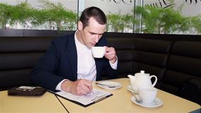 Businessman sitting in a cafe drinking coffee and writing documents stock footage