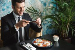 Businessman sitting in cafe take a photo of food by mobile phone. Image of a young businessman sitting in cafe take a photo of food by mobile phone stock image
