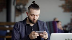 Businessman is sitting in cafe using smartphone. Male manager chatting at the table during the lunch typing text and. Bearded young businessman dressed in black stock video