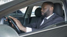 Businessman sitting in car and drumming fingers against steering wheel, anxiety. Stock footage stock footage