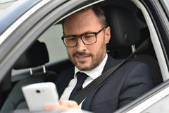 Businessman sitting in car and using smartphone Stock Image