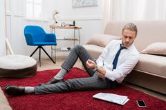 Businessman sitting on a carpet in a living room and reading. Newspaper Stock Photography