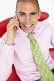 Businessman sitting and on a cellphone Royalty Free Stock Photo