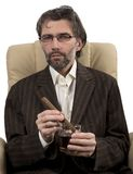 Businessman sitting in chair with cigar Royalty Free Stock Image